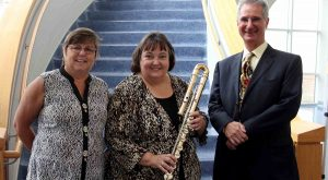 Catherine Robbins, Dr. Judy Hand, and David Robbins stand with the bass flute.