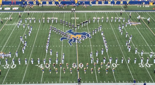 Up above view of McNeese band members in an M shape on the football field.