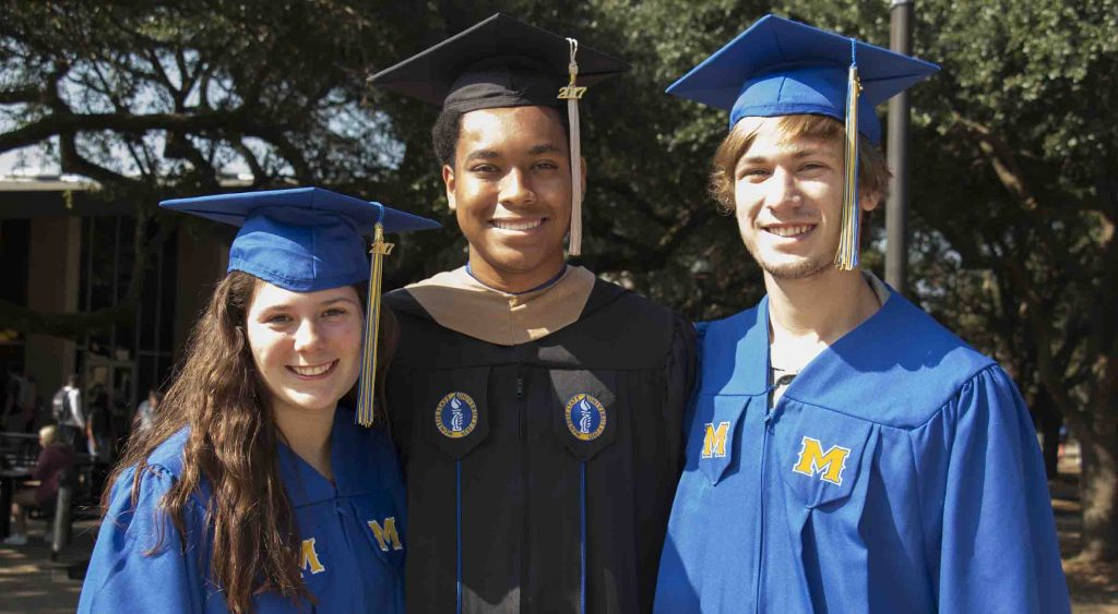 Students standing with new blue and black graduation robes.