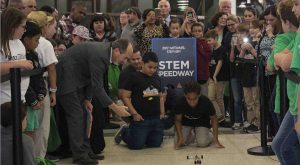 Dr. Nikos keeps time for two students racing their Mousetrap car as the audience looks on.