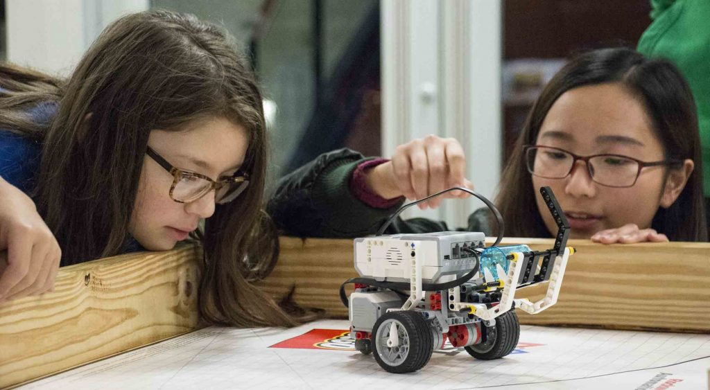 Huanrong Ouyang of McNeese helps 6th grader Ava Lankford with her robot.