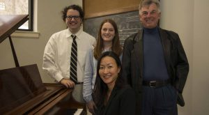 Dr. Lina Morita, Layton Bergstedt, Julianne Marler, and Bill Sherman gather around a piano.