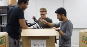 Austin Young, Ty Ellender, and Joseluis Botello-Esquivel of McNeese pack instruments into a large box.