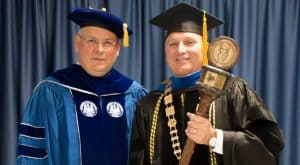 Dr. Burckel of McNeese stands with Dr. Henderson of University of Louisiana System wearing graduation regalia and holding the made