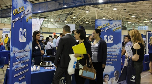 Students and alumni visit with a Career Fair sponsor.