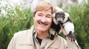 Peter Gros with a small animal on his shoulder.