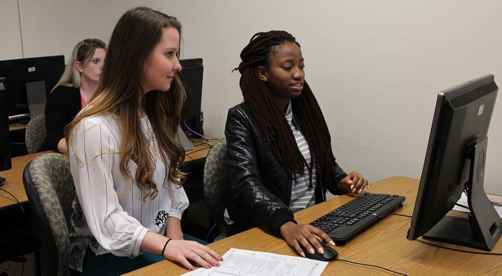 VITA intern Osauwen Osagie helps McNeese student Hannah Maust with her tax return.