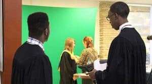Students stand in line to have their cap and gown photo taken