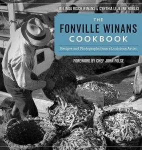 Man empties a sack of shrimp on The Fonville Winans Cookbook cover