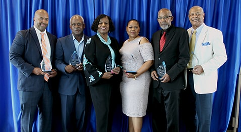 BAC recipients stand with their awards