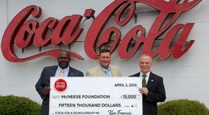 Ken Francis and Blaine Royer of Coca Cola stand with Eddie Meche of McNeese for the check presentation.