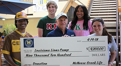 Koven Love, Austin Pottorff and Hailey Goodwin of McNeese present a check to Raymond Cecil of Louisiana Lions Camp.
