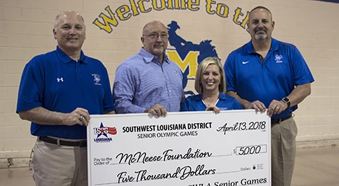 Dr. Burckel and Dr. Adrian and Dr. Soileau of McNeese accept a check from Angela Jouett of Southwest Louisiana District Senior Games.