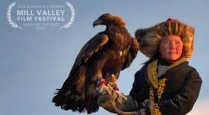 Aisholpan stands with an eagle on her hand