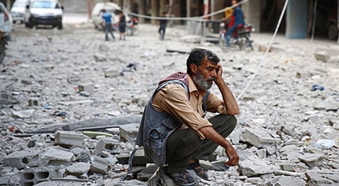 A man sits in the rubble of hard times in Syria
