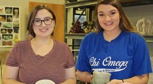 Shelby Roberie and Madison Augustine are pictured with some of their ceramic artwork.