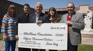 Melissa Northcutt of McNeese receives a check from the Rev. Nathan Long, Ashley Ivey-Atkins and Deacon Glenn Viau of St. Louis Catholic High School.