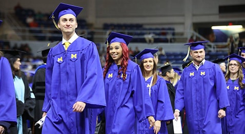 Graduation candidates walk to their seats.