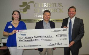 James David Cain Jr., McNeese Alumni Association president, accepts the donation from Heather Hidalgo and Kevin Holland of CHRISTUS Ocshner Health