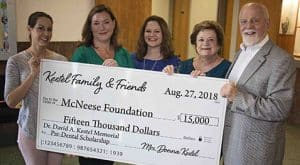 Dr. Caroline Hennigan and Richard Reid of McNeese accept a check from Amy Kestel, Stephanie Kestle Karpovs and Donna Kestel