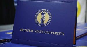 Blue diploma cover with McNeese gold seal and university name.