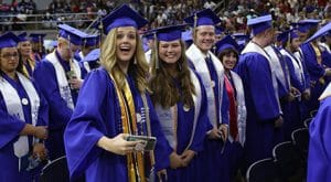Undergraduate students in blue gowns smile for the camera as they anticipate the start of graduation.