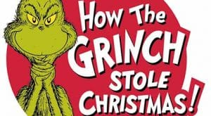 The Grinch stands smirking with the musical title to his right.