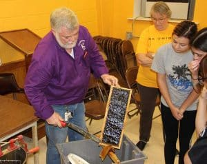 Local beekeepers show McNeese State University agricultural sciences students how to harvest the honey from the bee hives as part of the process of commercial honey production.