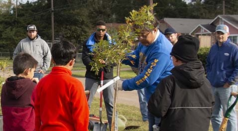 Volunteers watch how to dig and plant tree species.