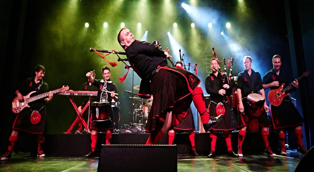 Red Hot Chilli Pipers perform with bagpipes on stage