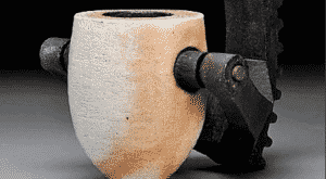 A stone cup is gripped by a piece of machinery