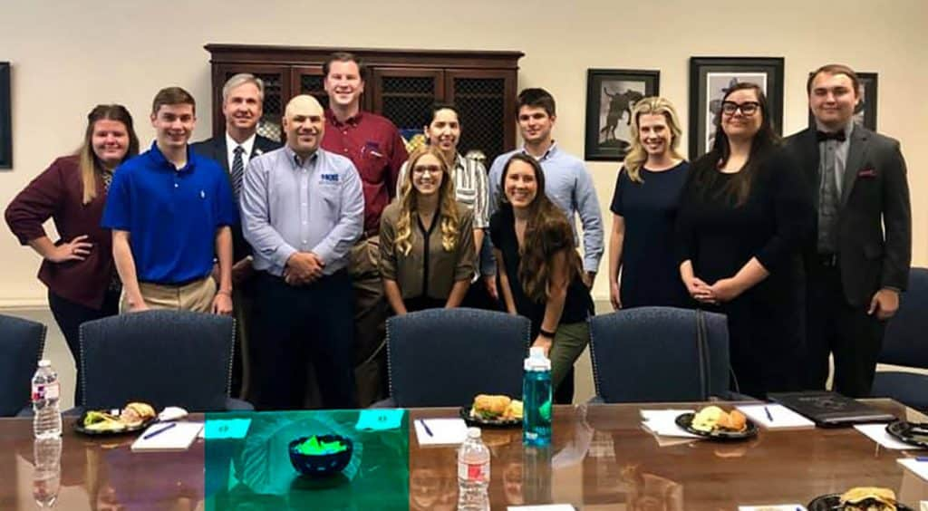McNeese students and faculty stand with MQB partners during the Lunch and Learn.