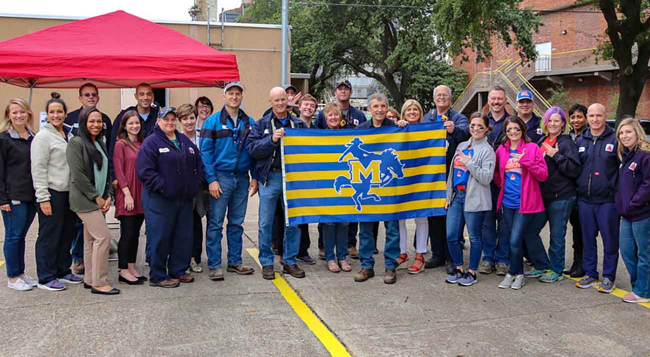 McNeese alumni currently working at CITGO proudly display the McNeese flag to be on display for the next year in front of the refinery.