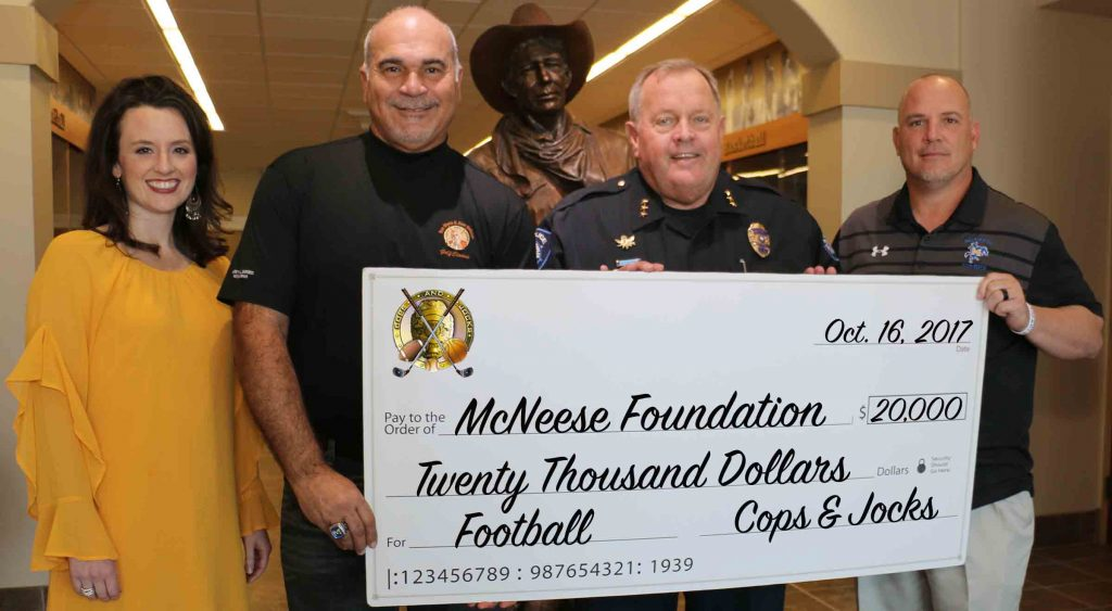 Alan Heisser and Don Dixon of Cops and Jocks present a check to Jennifer Leger and Lance Guidry of McNeese.