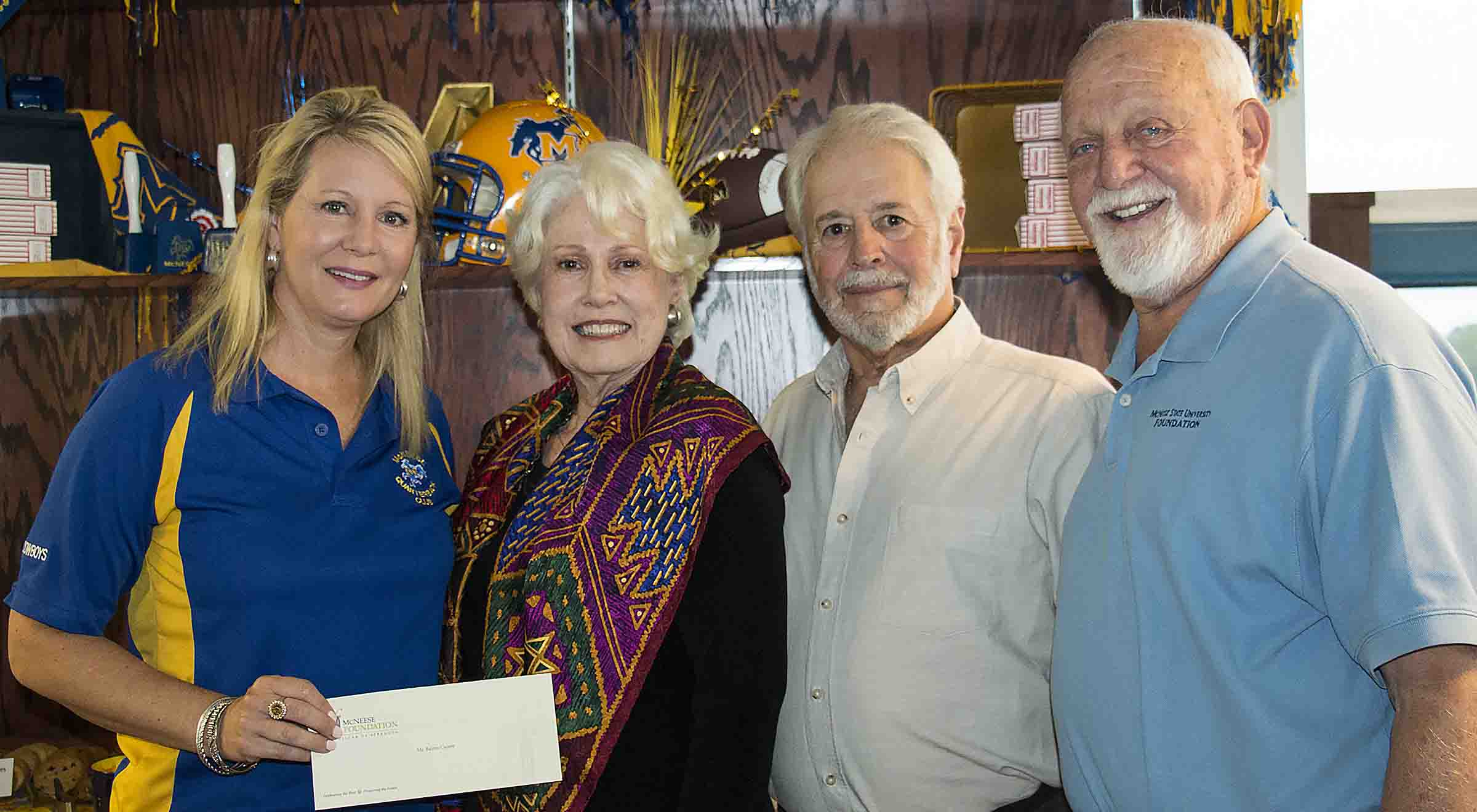 Angela Queenan and Richard Reid of McNeese accept a check from Anita and Jeff Webb.