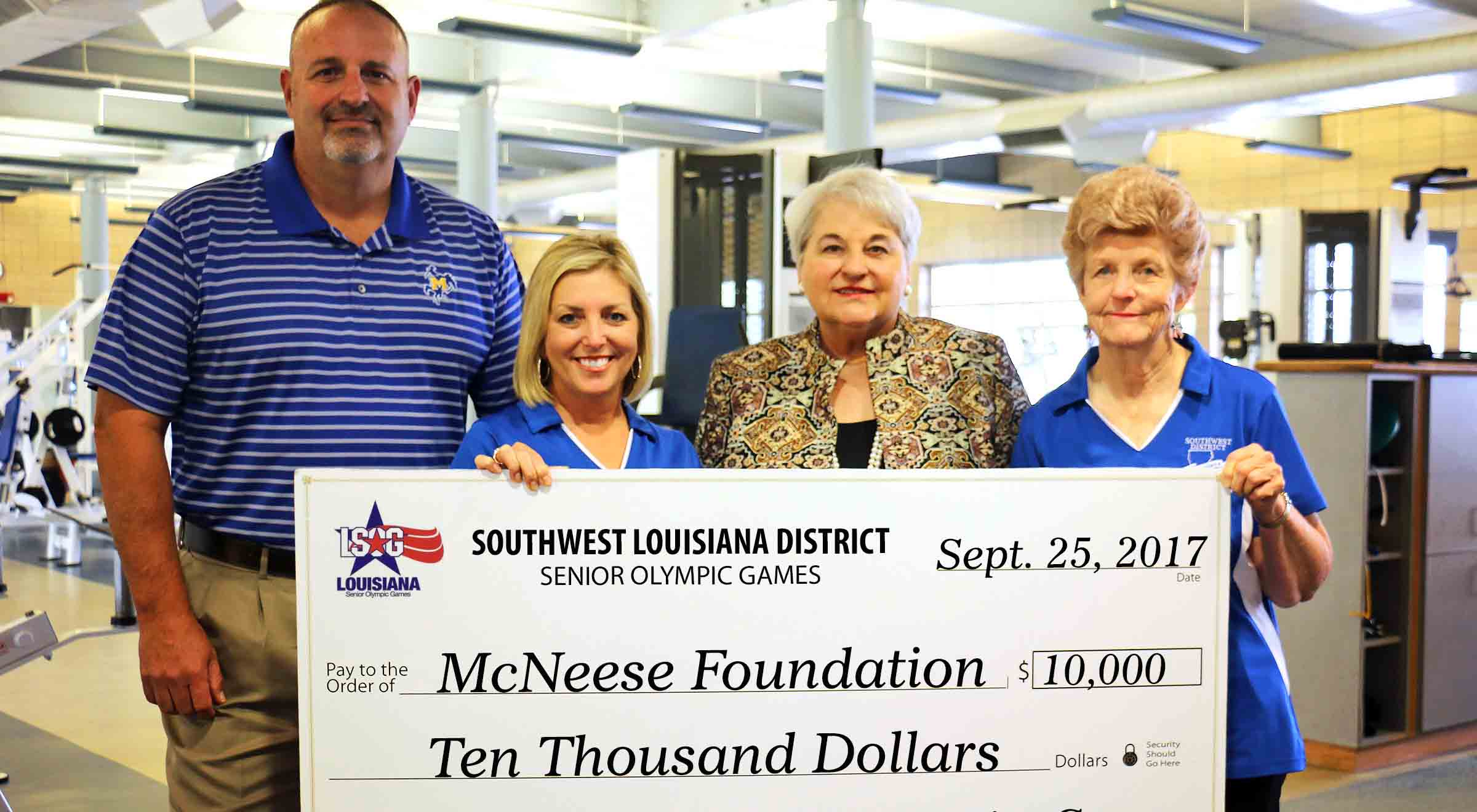 Senior Olympic Games members present a check to McNeese members in the Rec Center weight room.