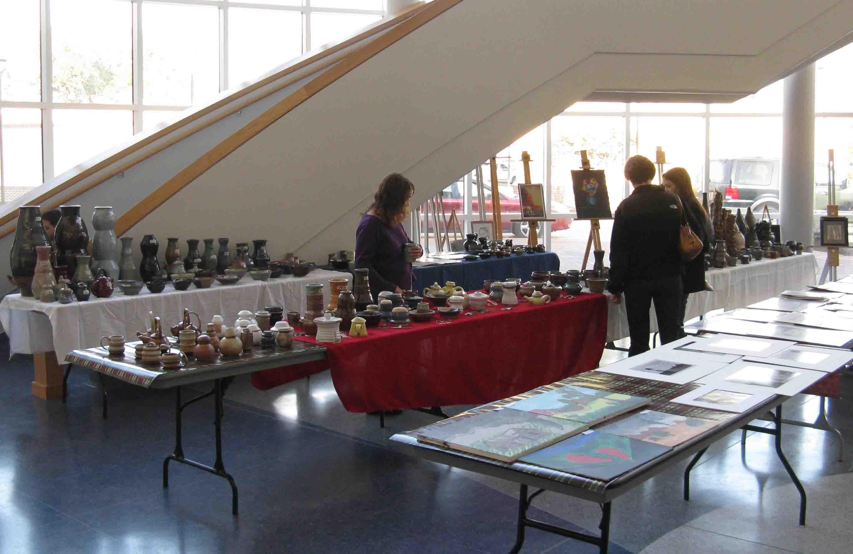 Art sale visitors admire student work on display.
