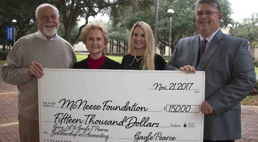 Richard Reid of McNeese accepts a check from Gayle Pearce, Stephanie Pearce Helms and Gary L Pearce Jr.