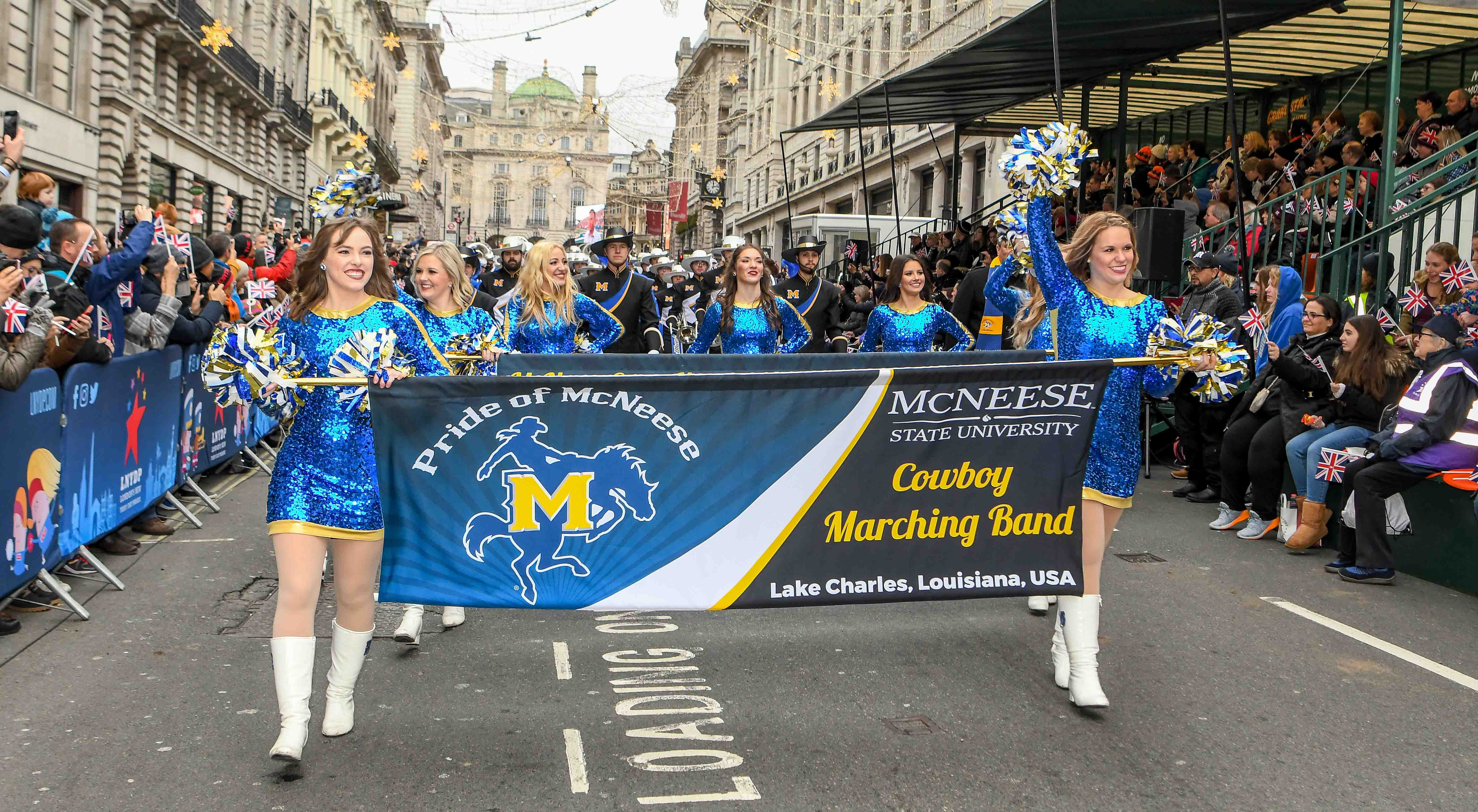 The McNeese Band and Cowgirl Kickers walk the streets of London in the parade.