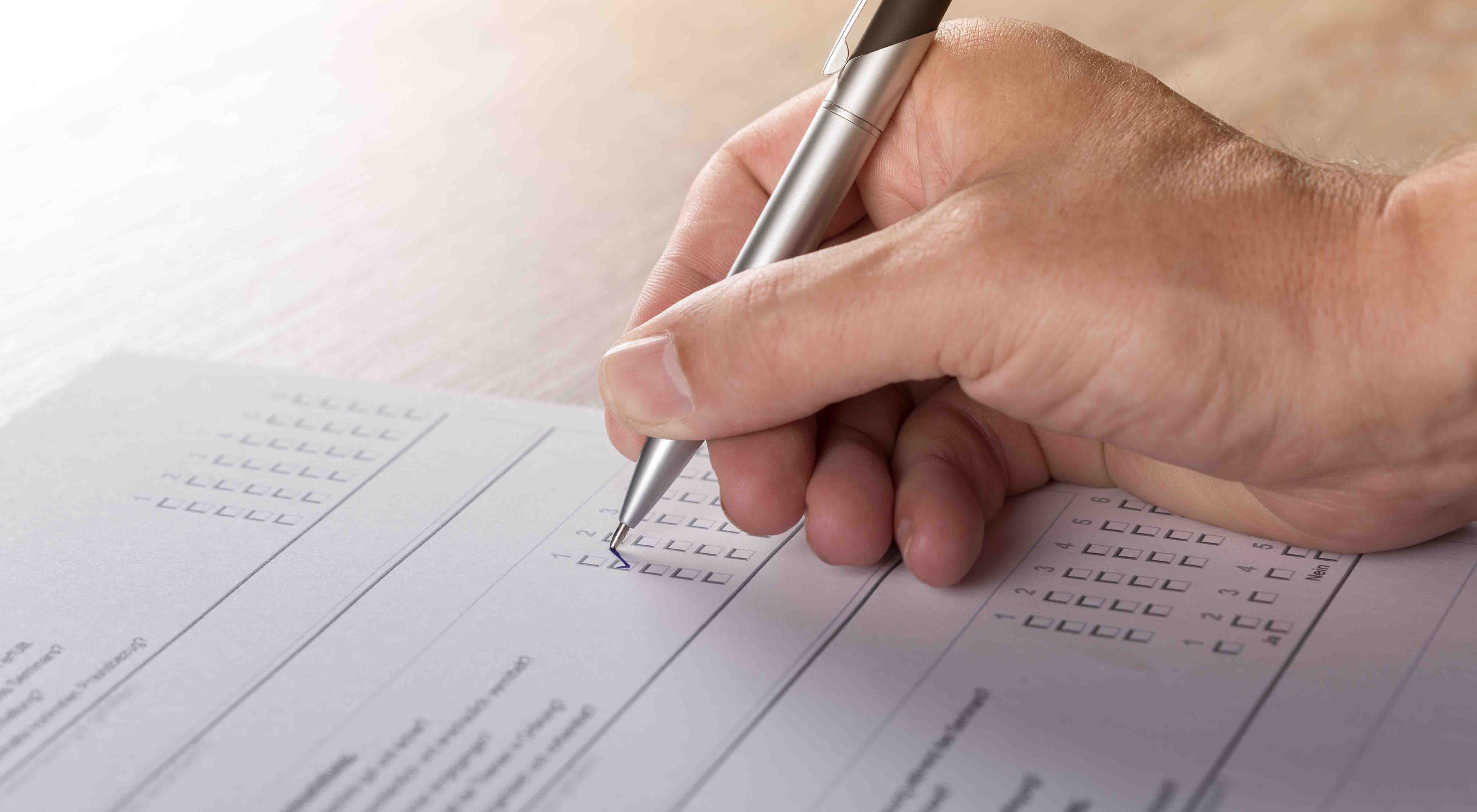 A hand is seen using a pen to mark on a test paper