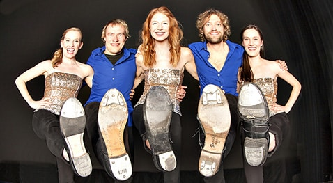 Members of The Step Crew stand with one leg up showing the bottom of their shoes.