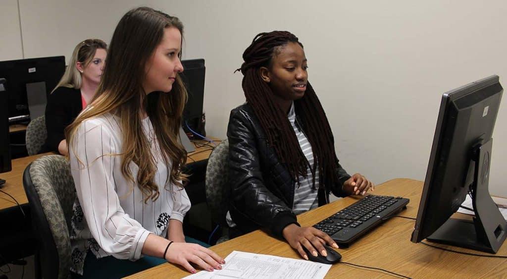 VITA intern Osauwen Osagie helps McNeese student Hannah Maust with her tax return.