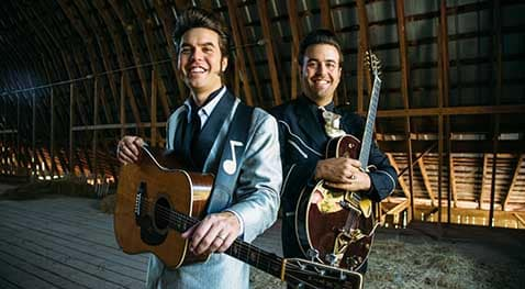 The Malpass Brothers stand with guitars