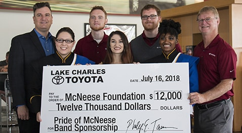 Eric, Corey and Phillip Tarver of Lake Charles Toyota present a check to Dr. Jay Jacobs of McNeese with three band members