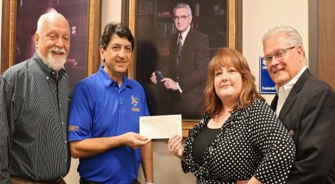 Richard H. Reid, vice president for university advancement and executive vice president of the foundation, Dr. Matthew Aghili, associate dean of the McNeese College of Engineering and Computer Science, and Karen and Ken Chamberlain. Karen's grandfather is the late Dr. Thomas S. Leary, McNeese's third president whose portrait is in the background.