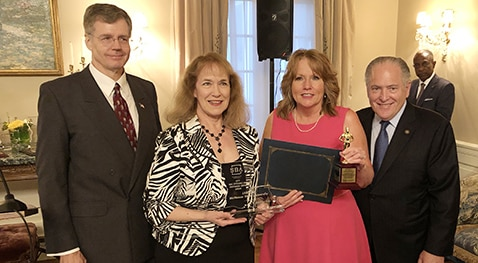 U.S. Small Business Administration Louisiana District Director Mike Ricks, along with Louisiana Economic Development Secretary Don Pierson, presents McNeese LSBDC Director Donna Little and Senior Business Consultant Susan Thibodeaux with the Region VI SBDC Excellence and Innovation Center award.
