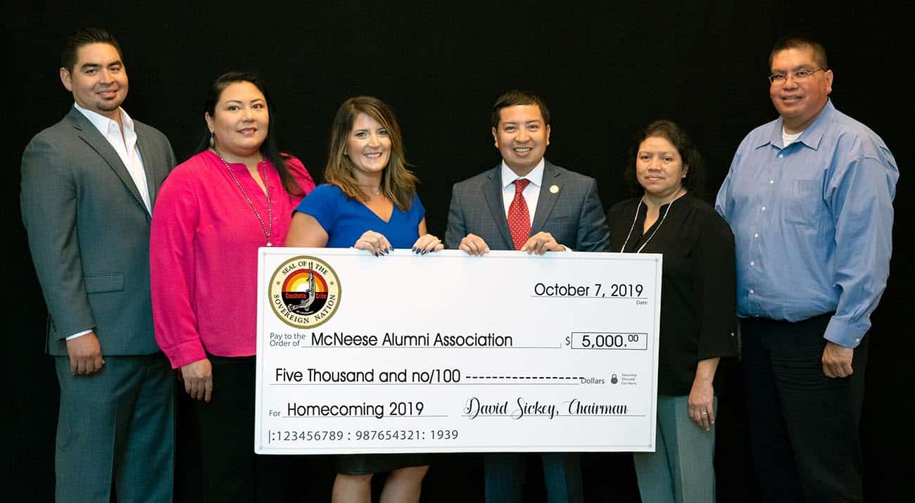 Stephanie Clark, third from left, assistant director for alumni affairs, receives the donation, from left, Johnathan Cernek, Coushatta Tribe of Louisiana councilman, Crystal Williams, councilwoman, David Sickey, chairman, Loretta Williams, secretary and treasurer, and Kevin Sickey, vice chairman.