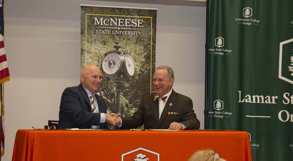 McNeese president Dr. Daryl Burckel and Lamar State College president Dr. Thomas Johnson sign the agreement.