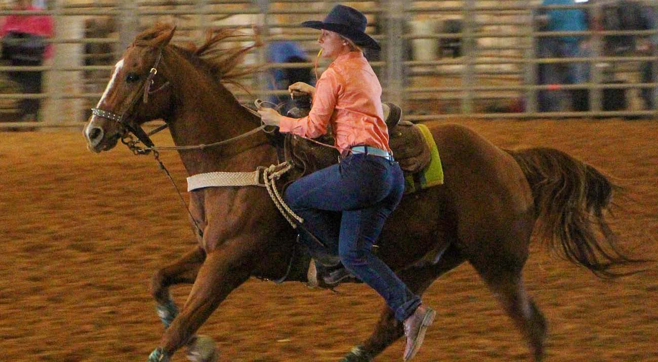 A rodeo team member descends from a horse to finish the event.
