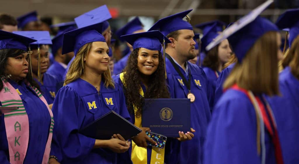 Graduates stand with their diploma covers as commencement ceremonies proceed.